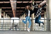 Due belle ragazze che saltano sulla stazione — Foto stock