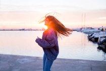 Милая женщина машет волосами на закате — стоковое фото