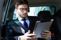 Businessman using tablet in car — Stock Photo