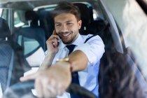 Улыбающийся водитель разговаривает по телефону — стоковое фото