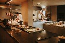 Cooks making dishes in restaurant kitchen — Stock Photo