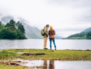 Couple of tourists looking in lake — Stock Photo