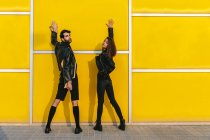 Fashion couple posing over yellow wall — Stock Photo