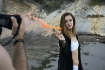 Homme tenant une fille de la photo avec de la fumée colorée sur la plage — Photo de stock