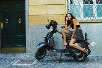 Stylish woman on scooter — Stock Photo