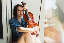Wonderful model with violin in sunlight — Stock Photo