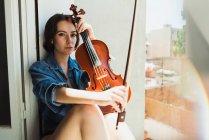 Прекрасная модель со скрипкой в солнечном свете — стоковое фото