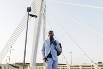 Stylish male model in suit with headphones — Stock Photo
