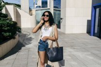 Pretty woman with smartphone in city — Stock Photo