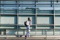 Trendiger Mann geht und telefoniert — Stockfoto