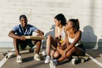Jóvenes comiendo pizza en la calle - foto de stock