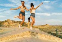 Счастливые женщины, прыжки на холме — стоковое фото