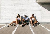 Tre giovani con assi in strada — Foto stock