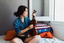 Schöne Frau mit Geige sitzend — Stockfoto