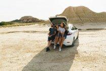 Amigos sentado na mala do carro — Fotografia de Stock