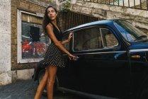 Женщина возле ретро-машины на улице — стоковое фото