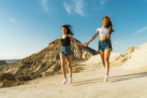 Happy women walking on hill — Stock Photo