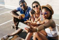 Fröhliche Freunde nehmen Selfie mit pizza — Stockfoto