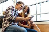 Ritratto di giovani coppie per mezzo del telefono mobile in strada — Foto stock