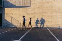 Couple de planches à roulettes à cheval sur la rue — Photo de stock
