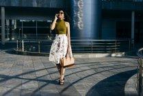 Cheerful woman talking phone on street — Stock Photo