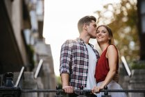 Young loving couple kissing in the street. — Stock Photo