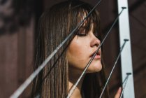 Woman standing at rope fence with eyes closed — Stock Photo