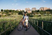 Mann mit Fahrrad über Boardwalk posiert — Stockfoto