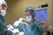 Retrato de cirurgiões fornecendo operação no hospital — Fotografia de Stock