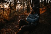 Man sitting at tree in forest and looking at sunset. — Stock Photo