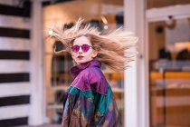 Young stylish girl in sunglasses looking back over shoulder with hair waving. — Stock Photo
