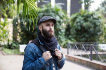 Portrait of bearded man in stylish outfit with backpack posing on background of street scene. — Stock Photo