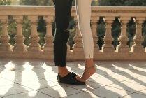 Crop of girlfriends legs standing foots on black boyfriends shoes . - foto de stock