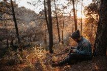 Uomo che si siede nella foresta e cercando in zaino — Foto stock