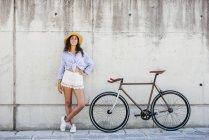 Jeune fille au chapeau se tenant à vélo — Photo de stock