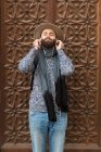 Portrait of bearded man plugging earphones with eyes closed over ornate bas-relief door — Stock Photo