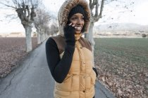 Smiling girl in jacket talking on smartphone at autumn park — Stock Photo