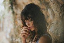 Porträt der hübsche Brünette Frau mit Augen geschlossen Tocuhing ihre Lippen mit den Fingern im freien gegen felsige Oberfläche — Stockfoto