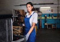 Ritratto del meccanico femminile con il cacciavite in mano rivolto verso l'obiettivo — Foto stock