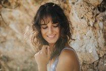 Porträt der zarte Brünette Mädchen lächelnd und blickte über Sandstein-Oberfläche — Stockfoto