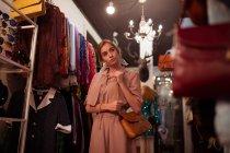 Stilvolle Mädchen in posiert auf Hintergrund der Kleidung Zimmer — Stockfoto