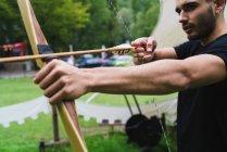 Crop man practicing archery in school — Stock Photo