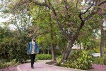 Joven melena de moda caminando por el sendero en el hermoso parque y mirando hacia otro lado - foto de stock