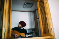 Cheerful bearded man in knitted hat playing acoustic guitar at home — Stock Photo