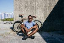 Человек с солнцезащитные очки, сидя возле велосипедов — стоковое фото