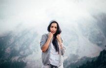 Брюнетка в толстовке позирует над туманным горным пейзажем — стоковое фото