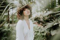Sensuale ragazza bruna posa a verde e guardando la fotocamera — Foto stock