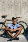Улыбающийся человек, сидящий рядом велосипедов — стоковое фото
