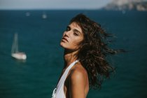 Portrait of brunette girl with windy hair posing over seascape with floating yachts — Stock Photo