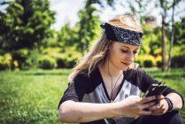 Woman skateboarder listening music from smartphone in park — Stock Photo